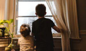 jongen en meisje kijken uit raam